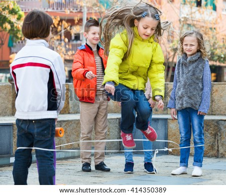 Smiling girl jumping while jump rope game with friends outdoor