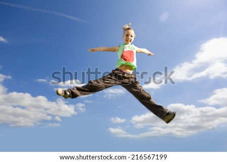 Smiling girl jumping with arms outstretched in sky - stock photo