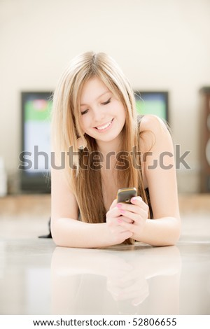 Smiling girl lies on floor and reads sms. - stock photo