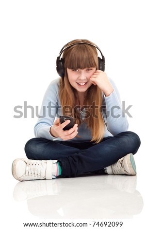 smiling girl listening to music on MP3 player isolated over white - stock photo