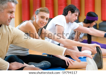 Smiling girl looking at camera during stretching exercises with her class at gym - stock photo