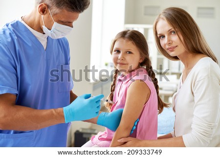 Smiling girl looking at camera while doctor making her an injection in clinics - stock photo