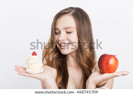 Smiling girl looking at cupcake and deciding to eat it instead of apple. Concept of human weakness