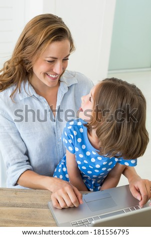 Smiling girl looking at mother using laptop at home