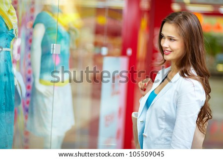 Smiling girl looking at the shop window before entering the store - stock photo