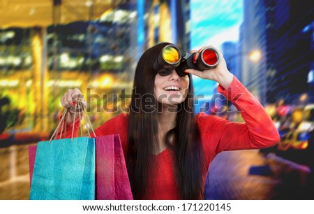 Smiling girl looking through the binoculars and looking for discount, city lights background - stock photo