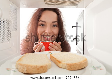Smiling girl looks in a microwave - stock photo