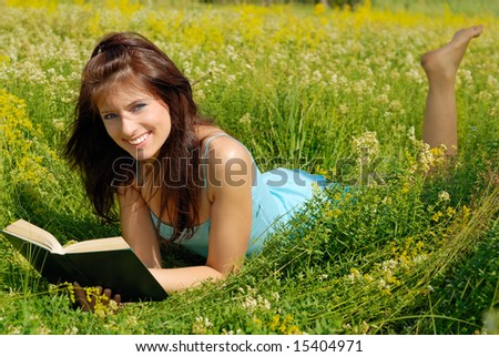 Smiling girl lying in a meadow with a book.