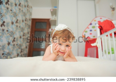 smiling girl lying in bed at her room - stock photo