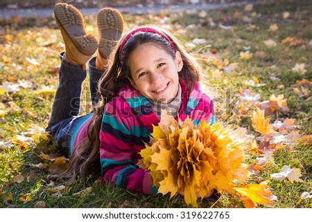 Smiling girl lying on grass with autumn leaves on autumn landscape - stock photo