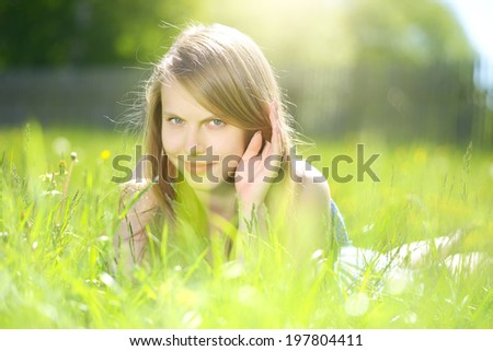 Smiling girl lying on the grass. light background