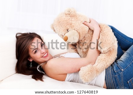 Smiling girl lying on the sofa with her teddy bear