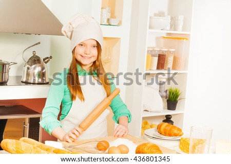 Smiling girl making bakery dough at the kitchen - stock photo
