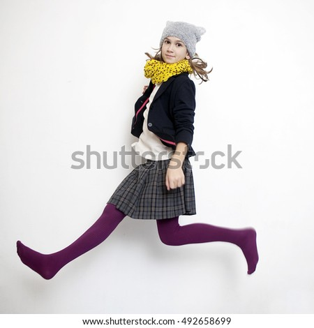 Smiling girl of eleven years in school uniforms jumping