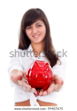 Smiling girl offering us a red piggy bank, focus on it