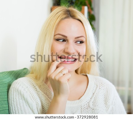 Smiling girl on couch having cunning look indoors