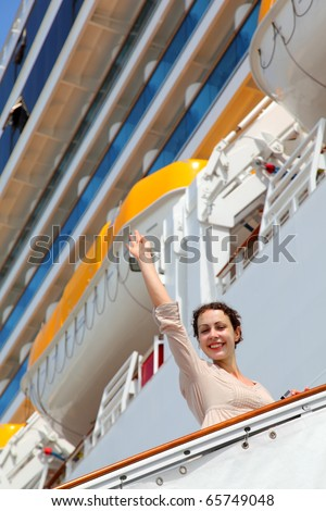 Smiling girl on ladder goes to cruise ship and wave by straight hand - stock photo