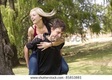 Smiling girl on piggyback of boy friend in park - stock photo