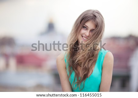 Smiling girl on roof - stock photo