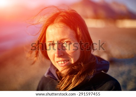 smiling girl on sea beach at the sunrise - stock photo