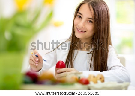 Smiling girl painting Easter eggs, holding brush and looking at camera  - stock photo