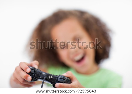 Smiling girl playing a video game against a white background - stock photo