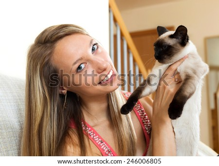 Smiling girl playing with a Siamese cat at home - stock photo
