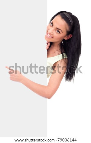 smiling girl pointing at a blank board, looking at camera, isolated on white background - stock photo