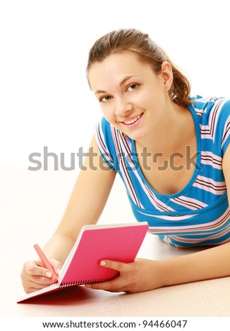 Smiling girl reading and making notes while lying on floor isolated