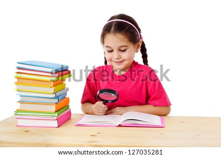 Smiling girl reading the books on the desk with magnifying glass, isolated on white - stock photo