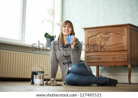 Smiling girl relaxing at home with a cup of tea - stock photo