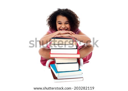 Smiling girl resting her arms on pile of books - stock photo