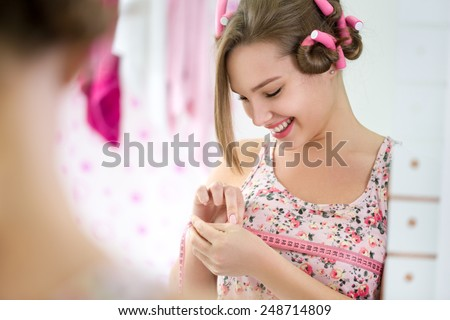 Smiling girl satisfied measuring her  breast - stock photo