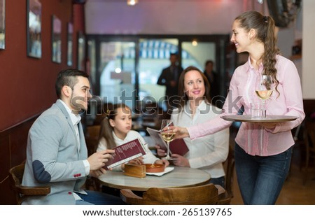 Smiling girl serving family of three at cafe table. Selective focus on girl