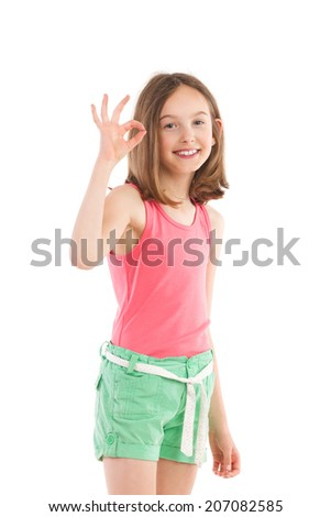 Smiling girl showing ok sign. Three quarter length studio shot isolated on white. - stock photo