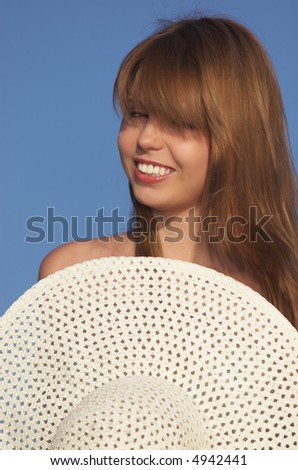 smiling girl sit with hat in hands - stock photo