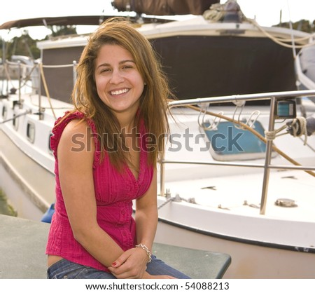 Smiling Girl siting next to a Boat in Dana Point Harbor - stock photo