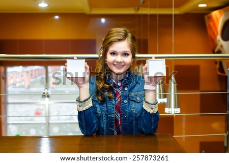 Smiling girl sits and shows the two halves of an empty white box - stock photo