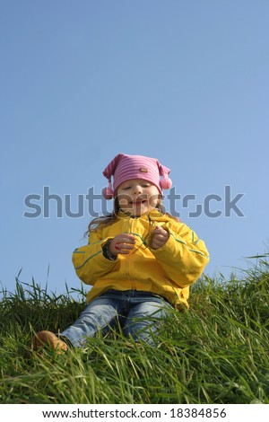 Smiling girl sits on a hill - stock photo