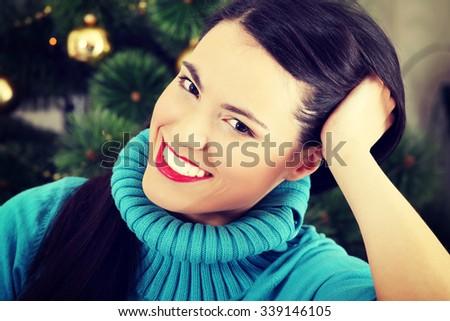 Smiling girl sitting at home on christmas - stock photo