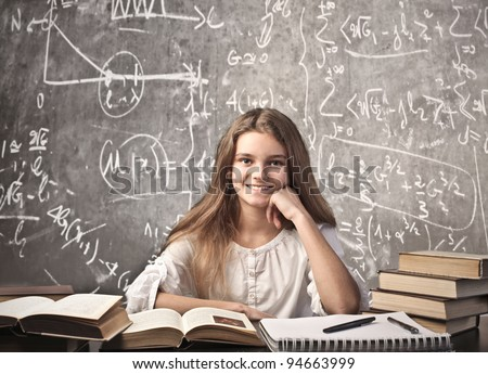 Smiling girl sitting in a classroom surrounded by books - stock photo