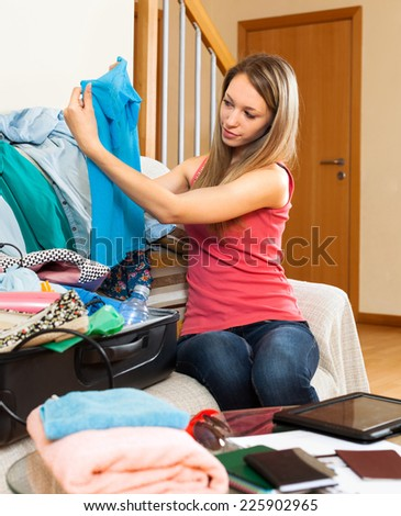 Smiling girl sitting in a room near the suitcase with clothes - stock photo