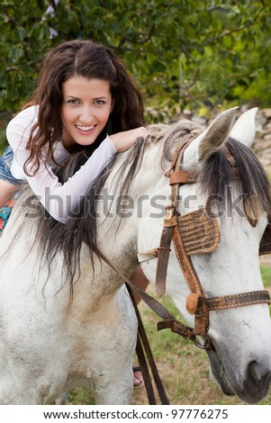 Smiling girl sitting on her favorite farm horse - stock photo