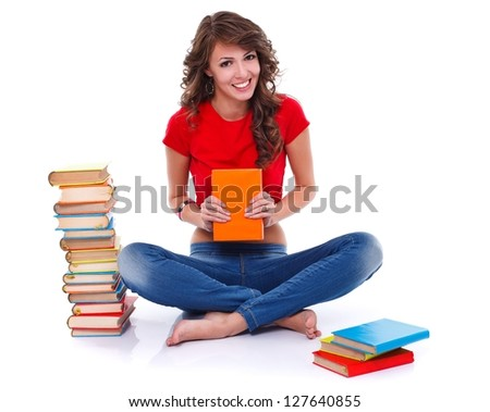 Smiling girl sitting on the floor with many colorful books, white background - stock photo