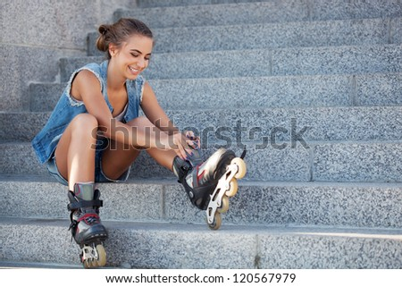 smiling girl sitting on the stairs and puts on skates - stock photo