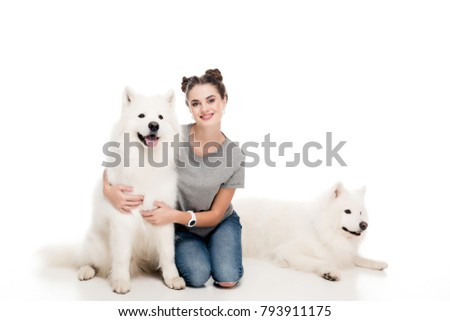 smiling girl sitting with dogs on white