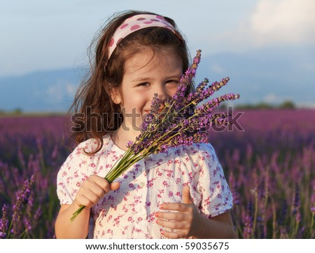 Smiling girl sniffing flowers in a lavender field - stock photo