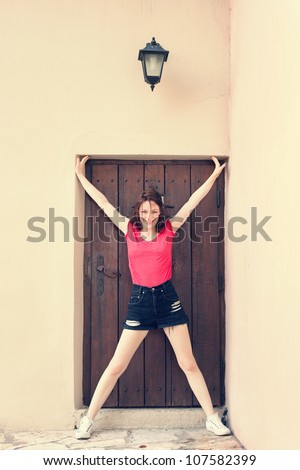 smiling girl stand with open arms and legs in door frame of old wooden door  in front old house, lantern above door - stock photo