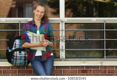 Smiling girl standing against a wall of her school