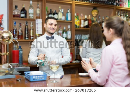 Smiling girl standing at bar with cup of coffee. Focus on guy - stock photo